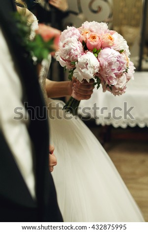 Gorgeous bride in elegant white dress holding wedding roses bouquet close-up - stock photo