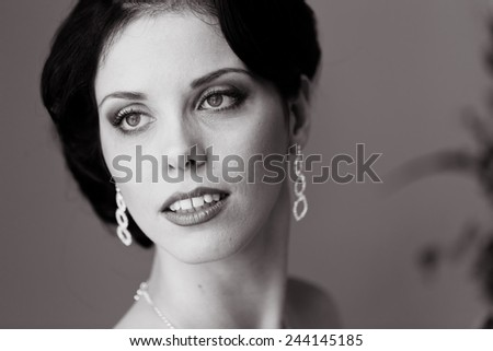Gorgeous bride in wedding dress in luxury interior with diamond jewelry posing at home and waiting for groom. Romantic rich happy girl in bridal dress smiling have final preparation for wedding