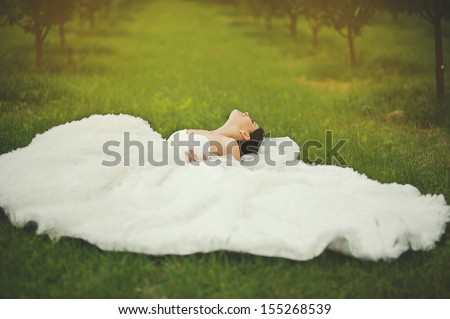 gorgeous  bride laying in garden, summertime - stock photo