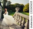 gorgeous bride outdoors playing with wedding dress - stock photo