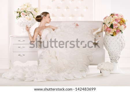 Gorgeous bride standing on sofa - stock photo