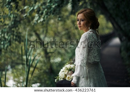 Gorgeous bride stands thoughtful holding a wedding bouquet over a fence - stock photo