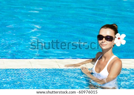 gorgeous brunette enjoying the sun in pool, space for copy - stock photo