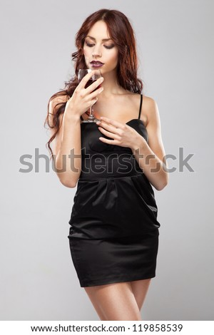 Gorgeous brunette in black dress with a glass of wine - stock photo