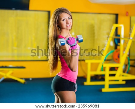Gorgeous brunette lifting some weights and working on her biceps in a gym - stock photo