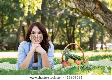 Gorgeous brunette lying on a mat with basket full of fruits in the park.
