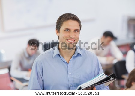 Gorgeous brunette male teacher posing in his classroom holding some files smiling at camera - stock photo