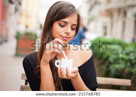 Gorgeous brunette tourist girl having coffee on the street. - stock photo
