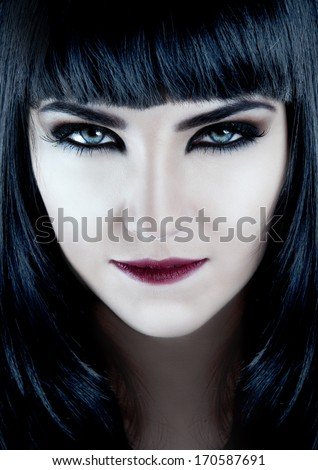 Gorgeous brunette with dark makeup and white skin - stock photo
