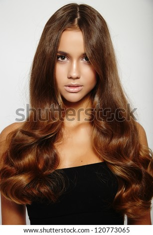 Gorgeous brunette young woman with long glamorous hair - stock photo