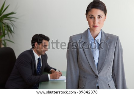 Gorgeous businesswoman posing while her colleague is working in an office - stock photo