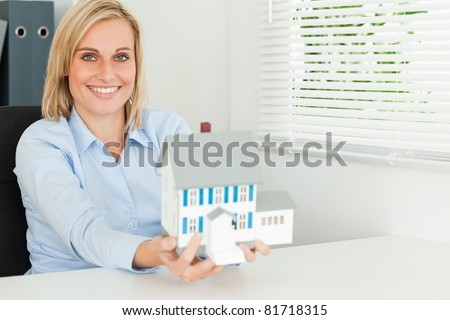 Gorgeous businesswoman presenting model house looking into the camera in her office - stock photo