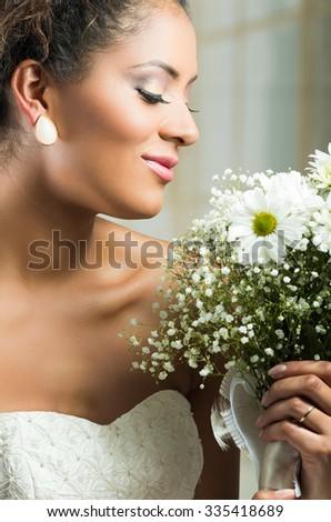 Gorgeous closeup portrait of African American bride holding flower bouquet - stock photo