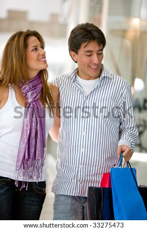 gorgeous couple shopping looking at a window and smiling - stock photo