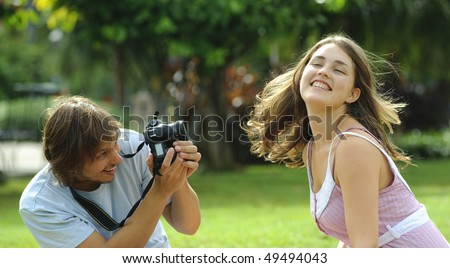 Gorgeous couple take pictures in the park - stock photo