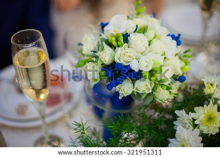 gorgeous decorated wedding table with bouquet and a glass of champagne in a restaurant - stock photo