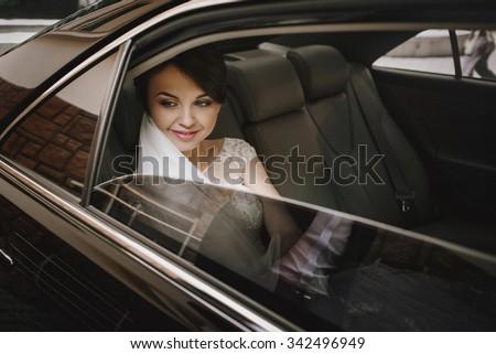 gorgeous elegant happy stylish brunette bride in luxury car on the background of restaurant - stock photo