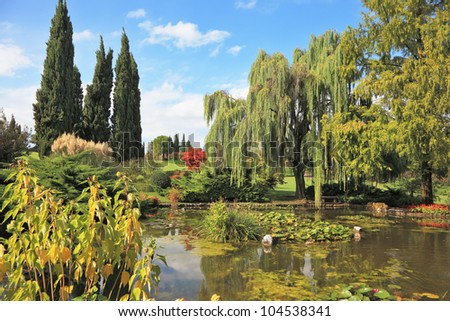 Gorgeous European park. Quiet picturesque pond surrounded by bright green shrubs and trees - stock photo