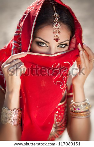 gorgeous eyes of young indian woman in traditional clothing with bridal makeup and jewelry. Beautiful bride traditionally dressed Outdoors in India. Girl bollywood dancer in Sari. Arabian bellydancer - stock photo
