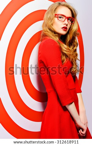 Gorgeous fashion model in red dress and elegant red glasses posing over red circles of the target. Beauty, fashion. Optics, eyewear. - stock photo