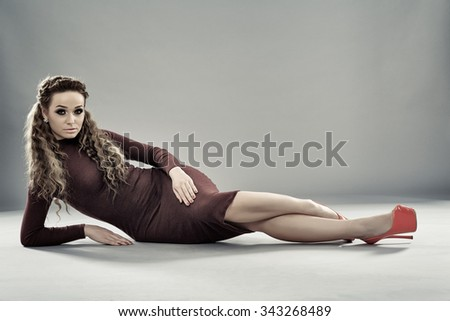 Gorgeous fashion model in tight dress and high heels posing on gray background
