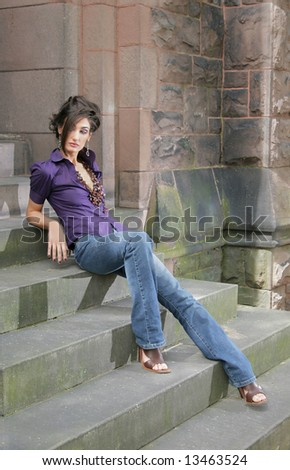 gorgeous fashion model sitting on old stone stairs