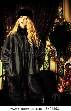 Gorgeous fashion model with magnificent blonde hair in a rich historical costume. Fur clothing. Vintage. Luxury style.  - stock photo