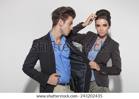 Gorgeous fashion woman looking at the camera while pulling her lovers jacket. He is looking at ther. - stock photo