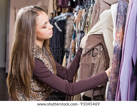 Gorgeous fashionable young brunette shopping around for new clothes.