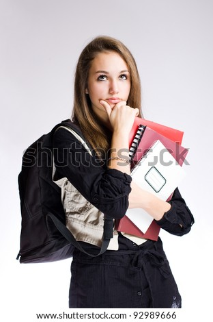 Gorgeous fashionable young student girl in pondering posture. - stock photo