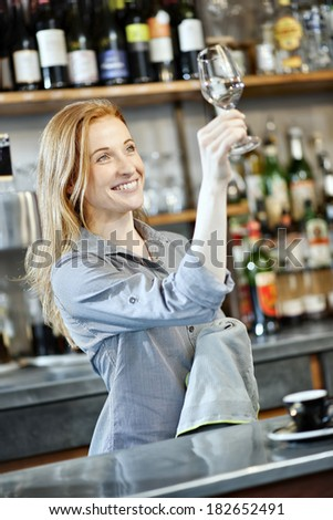 gorgeous female bartender wiping a glass in a bar