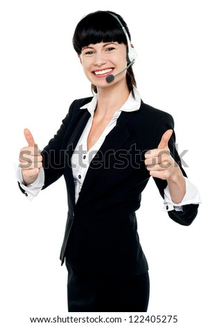 Gorgeous female customer support agent with headsets on showing double thumbs up - stock photo