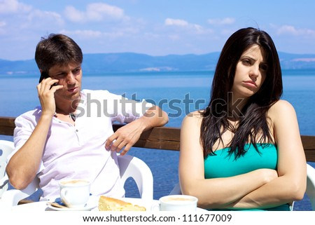 Gorgeous female model annoyed and frustrated by boyfriend on the phone - stock photo