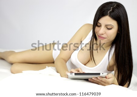Gorgeous female model happy reading ipad tablet - stock photo