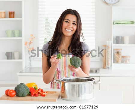 Gorgeous female preparing vegetables while standing in the kitchen - stock photo
