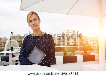 Gorgeous female sits in cozy coffee shop in the fresh air and holds portable touch pad with blank copy space screen, attractive woman employer waits in restaurant professionals to spends interview - stock photo