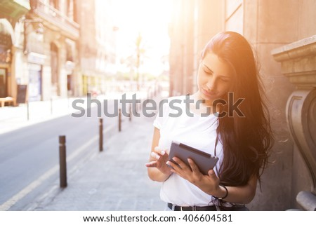 Gorgeous female tourist is using digital tablet for navigation during summer trip abroad, charming woman wanderer is searching information in network on touch pad while is standing on the city street  - stock photo