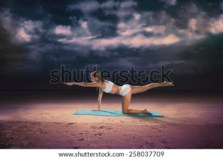 Gorgeous fit blonde in pilates pose on the beach against dark cloudy sky - stock photo
