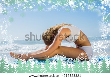 Gorgeous fit blonde in seated forward bend pose on the beach against snow - stock photo