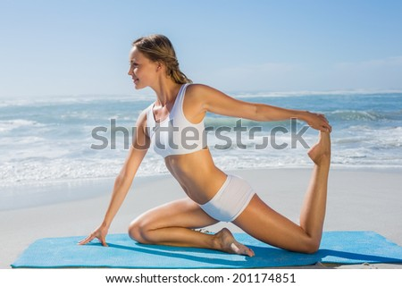 Gorgeous fit blonde in seated yoga pose on the beach on a sunny day - stock photo