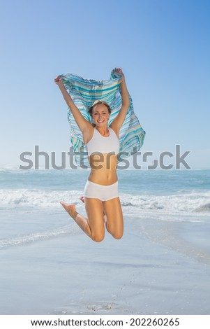 Gorgeous fit blonde jumping by the sea with scarf on a sunny day - stock photo
