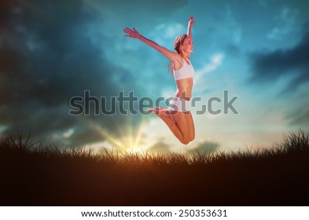 Gorgeous fit blonde jumping with arms out against blue sky over grass - stock photo