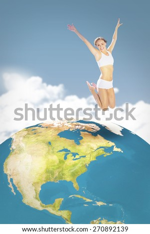 Gorgeous fit blonde jumping with arms out against night sky - stock photo