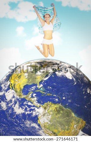 Gorgeous fit blonde jumping with scarf against blue sky - stock photo