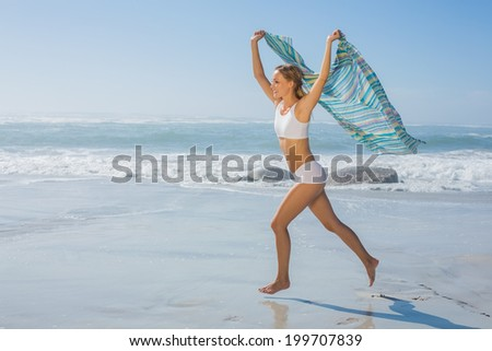 Gorgeous fit blonde running by the sea with scarf on a sunny day - stock photo