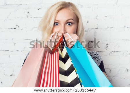 Gorgeous girl  absolutely happy with new purchases and hiding behind them. Amazing blue eyes peeping out of shopping bags - stock photo
