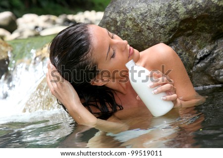 Gorgeous girl in river applying hair conditioner