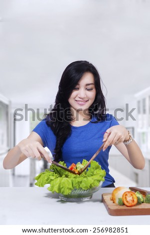 Gorgeous girl makings healthy meal from fresh vegetables in the kitchen - stock photo