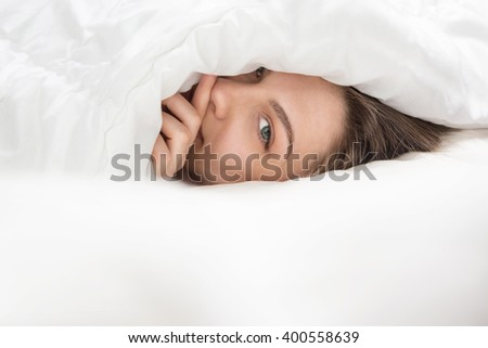 Gorgeous girl peeping from under the white blanket. Sunny pleasant morning. time to wake up. Start a new wonderful day. lovable green eyes looking - stock photo