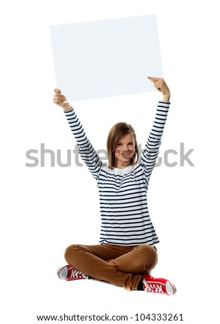 Gorgeous girl pointing at blank white clipboard over her head - stock photo